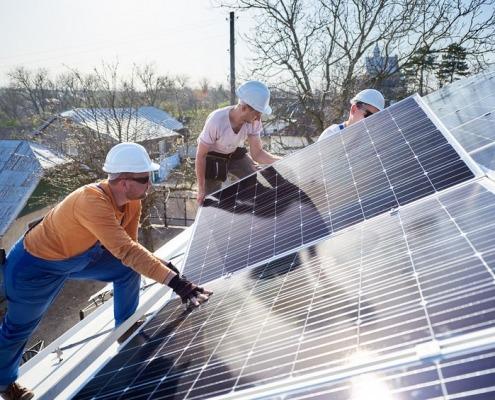 Lavoratori che installano un sistema di pannelli solari fotovoltaici. Elettricisti che montano il modulo solare sul tetto della casa moderna. Concetto ecologico di energia alternativa.