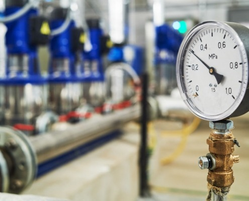Primo piano del manometro, tubi e valvole del rubinetto del sistema della stazione della pompa dell'acqua